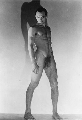 Yul Brynner standing in strong upward light